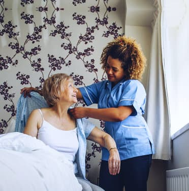 caregiver assisting senior woman on wearing dress