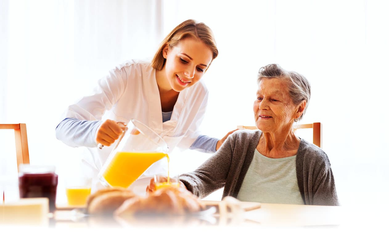 female caregiver serving juice to senior woman