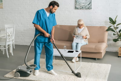 caregiver cleaning carpet and senior woman reading the newspaper