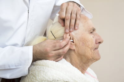 caregiver cleaning the ear of senior woman